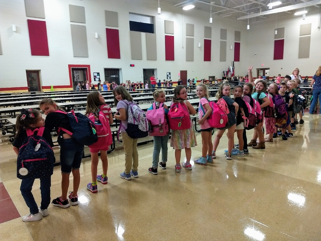 students showing off new backpacks
